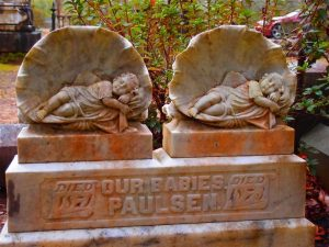A rusted sculpture of two babies sleeping.