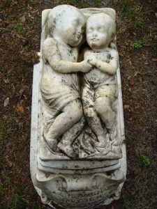 A grave with a sculpture of two sleeping children.