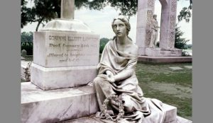 A gravestone next to a sculpture of a woman, both made of white marble.