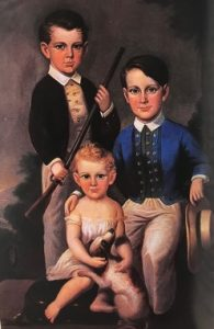 A portrait of 3 young boys. The oldest stands, holding a gun. The younger two sit, with the youngest petting a small black and white dog.