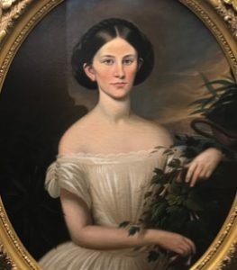 A portrait of a young woman with dark hair and a white dress. She lays her hands on green plants on the right side of the canvas.