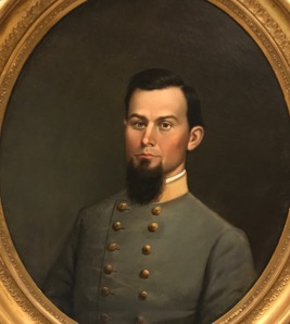 A portrait of a Confederate Captain with dark hair and a long beard in his grey uniform. He is placed in a round frame against a dark brown background.