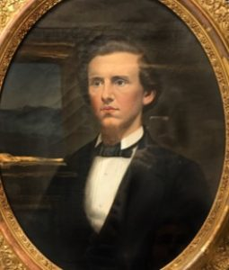A painted portrait of a caucasian man in a black and white tuxedo. He sits against a dark brown background.