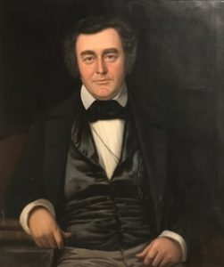 A portrait of an older man in formalwear. He has dark hair and thick eyebrows, and sits against a dark background.