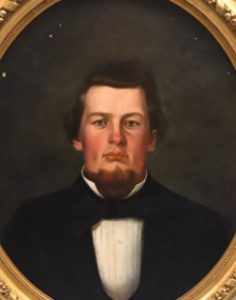 A portrait of a man with brown hair. He wears a tuxedo and is placed against a flat grey background.
